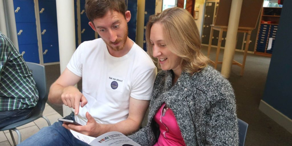 a man and a woman looking at a Streams leaflet at Poole Christian Fellowship